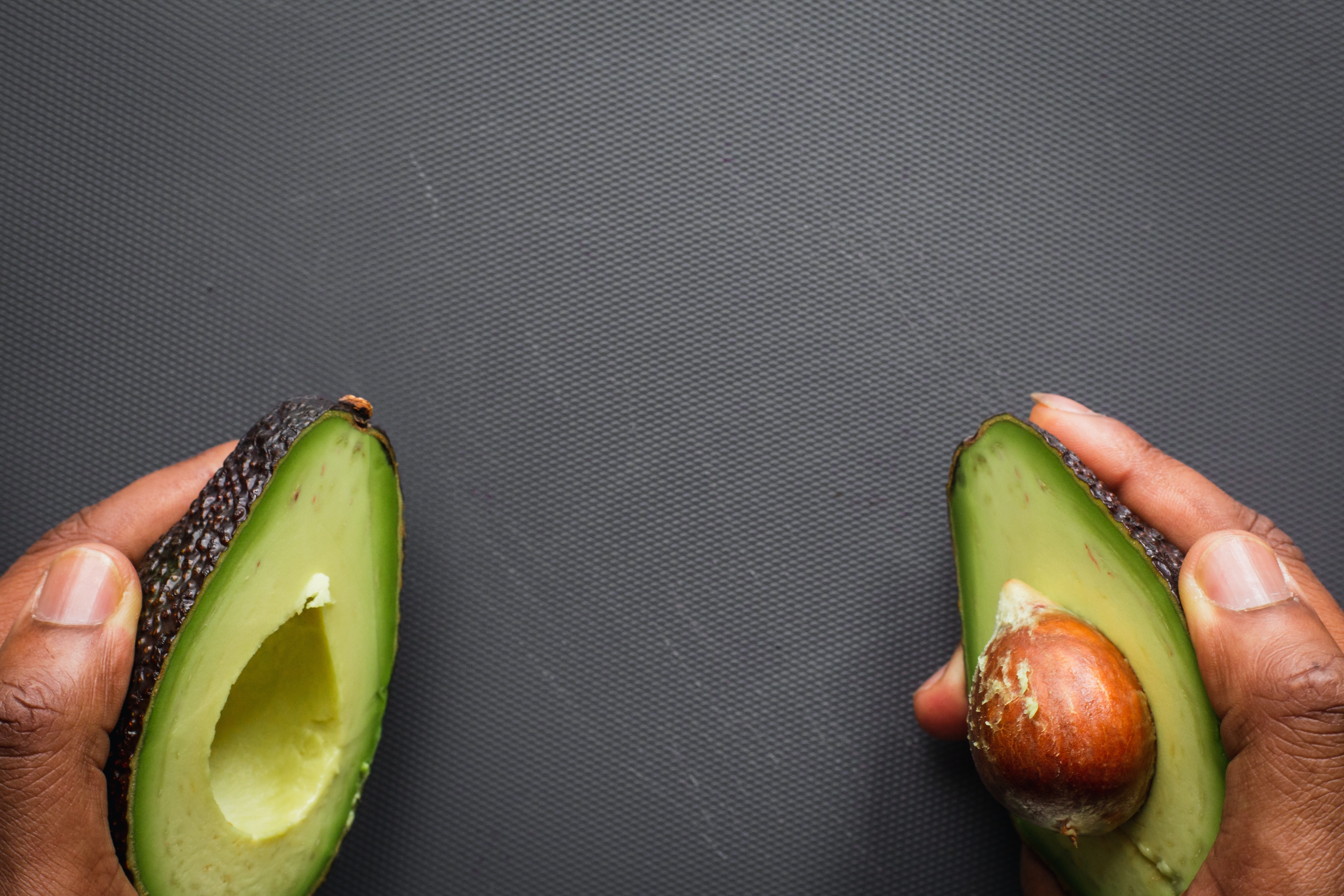 a person holding an avocado cut in half